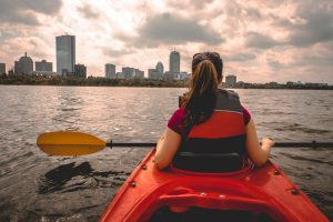 A woman in a red kayak stops along the Charles River to view the Boston skyline in the distance.