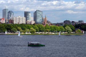 A duck tour boat can be seen traveling along the Charles River. Several sailboats can be seen around it. A line of trees and part of the Boston skyline are visible past the lake.