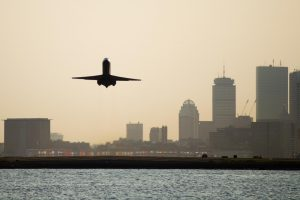 A commercial plane takes off from a ramp at Logan International Airport. The Boston city skyline and a cloudy sky can be seen in the background.