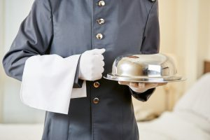 A closeup shot of a hotel butler in a room. You can see a white napkin draped over his left forearm, and a silver plate of food in his right hand.