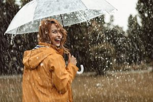 A red-haired woman with a clear umbrella and orange raincoat turns back to the camera and smiles. It is pouring rain around them. In the background you can see grass and trees.