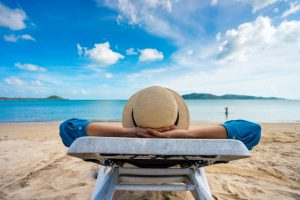 A view of a woman in a sunhat and blue shirt relaxing on a beach chair. In the background, you can see the sand, ocean and sky.