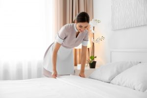 A maid in uniform fixes the white sheets on a hotel room bed.